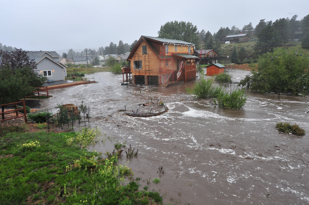 . A house with people still inside is completely surrounded by the Fish Creek on Thursday, September 12, 2013. Flooding closed roads and neighborhoods around Estes Park as heavy rain soaked the entire Front Range. Walt Hester/Estes Park Trail-Gazette