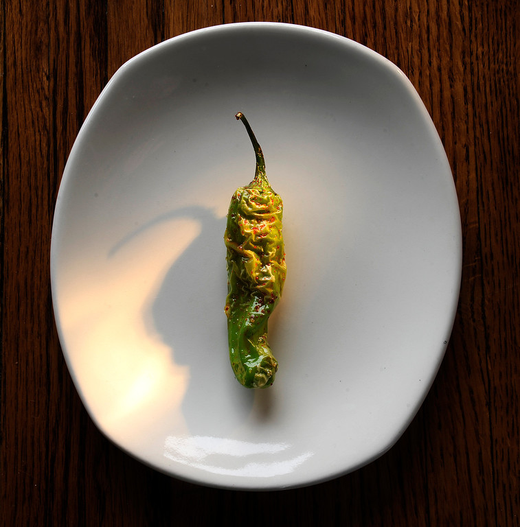 Description of . DENVER, CO. -  JULY 9:  A small handheld flashlight is used to light this shishito pepper at the restaurant Linger in Denver on Tuesday, July 9, 2013. The best part of the light was the shadow. Shishito peppers are  a small, thin skinned  Japanese peppers.  (Photo By Cyrus McCrimmon/The Denver Post)
