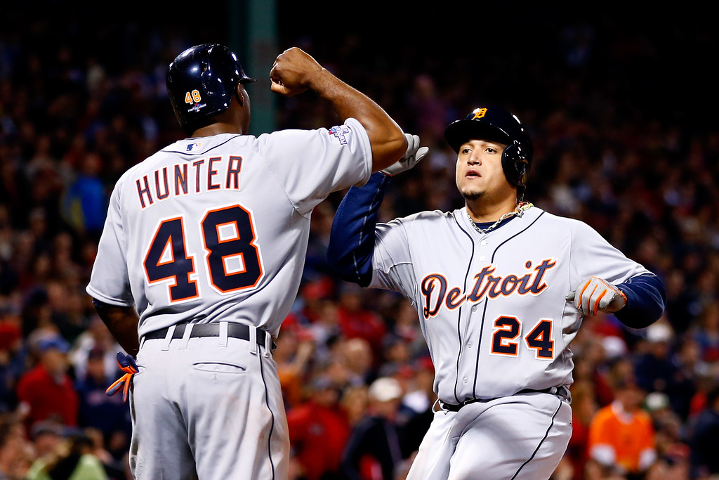 . Miguel Cabrera #24 and Torii Hunter #48 of the Detroit Tigers celebrate scoring on Victor Martinez #41 hit a single to deep left center against Franklin Morales #56 of the Boston Red Sox in the sixth inning during Game Six of the American League Championship Series at Fenway Park on October 19, 2013 in Boston, Massachusetts.  (Photo by Jared Wickerham/Getty Images)