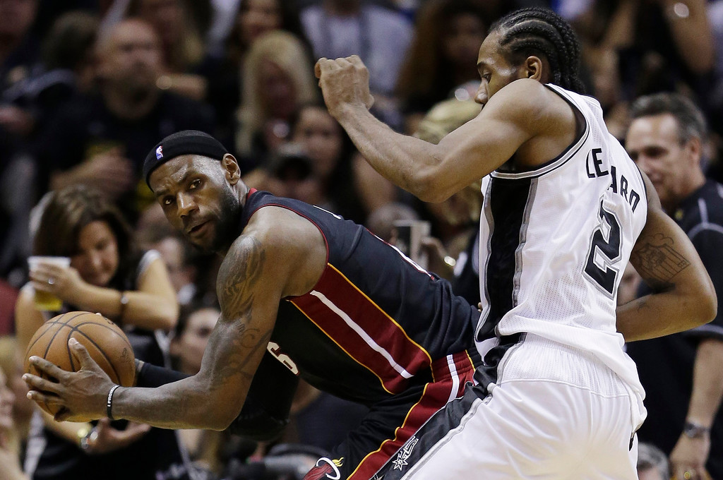 . Miami Heat forward LeBron James (6) looks past defender San Antonio Spurs forward Kawhi Leonard (2) during the second half in Game 5 of the NBA basketball finals on Sunday, June 15, 2014, in San Antonio. (AP Photo/David J. Phillip)