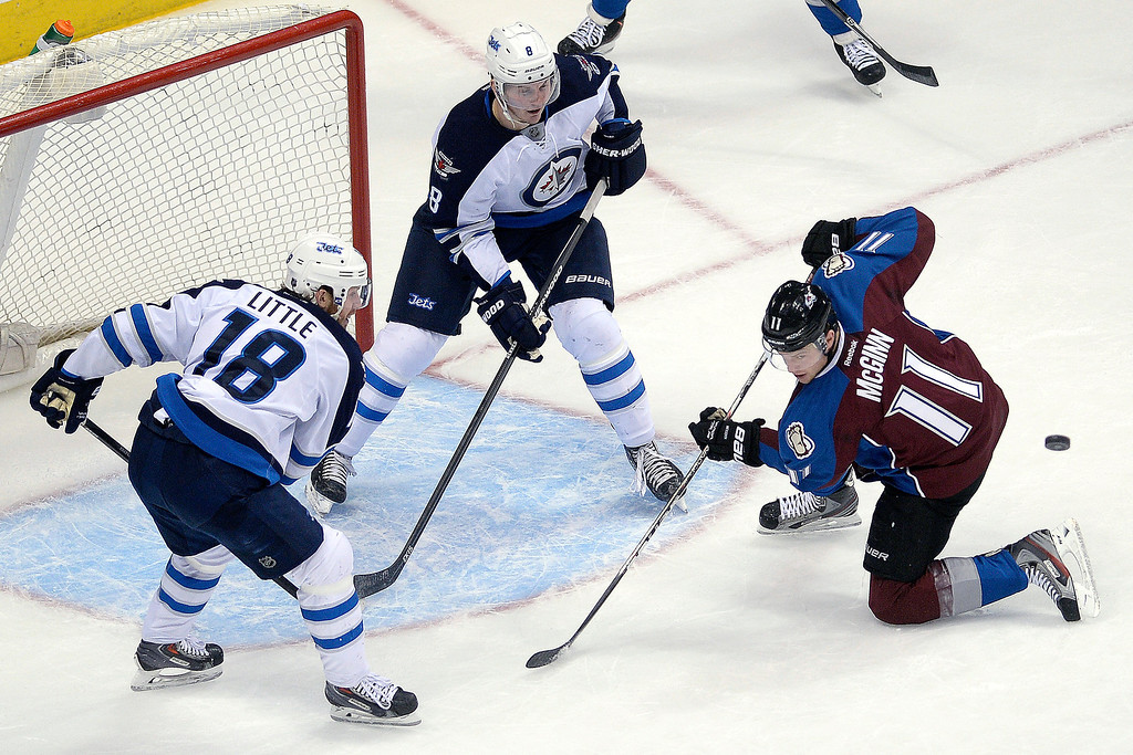 . Jacob Trouba (8) of the Winnipeg Jets and Bryan Little (18) defend the goal as Jamie McGinn (11) of the Colorado Avalanche attempts to wrangle the puck during the first period. (Photo by AAron Ontiveroz/The Denver Post)