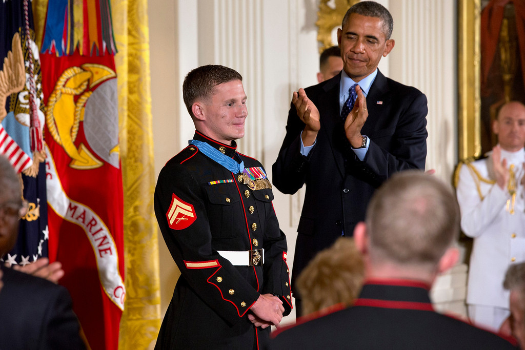 """. President Barack Obama and the crowd applaud retired Marine Cpl. William \""""Kyle\"""" Carpenter, 24, left, after awarding him the Medal of Honor for conspicuous gallantry, Thursday, June 19, 2014, during a ceremony in the East Room of the White House in Washington.  (AP Photo/Jacquelyn Martin)"""