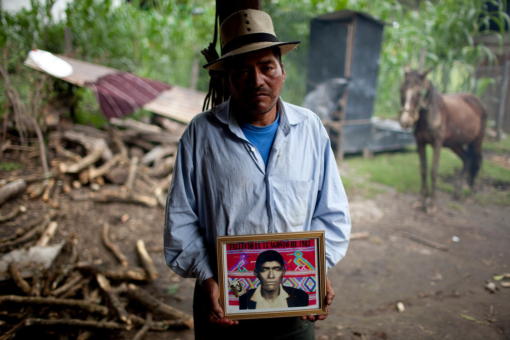 ". In this July 23, 2011, file photo, Tomas Raymundo Perez poses for a picture with a portrait of his father that reads ""Died Aug. 13, 1982\"" at his home in the municipality of Nebaj in Guatemala. Guatemalan soldiers allegedly killed Perez\'s family during a 1982 raid in the community of Vivitz. Twenty-nine years later, in June 2011, the Public Ministry brought charges against Gen. Hector Mario Lopez Fuentes in connection with the planning and ordering of bloody military operations that were part of the military plan coined \""Victoria 82,\"" among other crimes during his time as the Defense Ministry\'s Chief of Staff, including the extermination of residents in villages within the municipality of Nebaj during the government of Efrain Rios Montt (1982-1983). (AP Photo/Rodrigo Abd, file)"