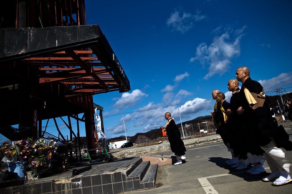 . Japanese Buddhist monks chant and pray in front of the remaining structure of a former disaster center to commemorate the second anniversary of the Great East Japan Earthquake and Tsunami on March 11, 2013 in Minamisanriku, Miyagi Prefecture, Japan. Japan is commemorating the second anniversary of the 2011 Magnitude 9.0 earthquake and subsequent tsunami that claimed more than 18,000 lives.  (Photo by Athit Perawongmetha/Getty Images)
