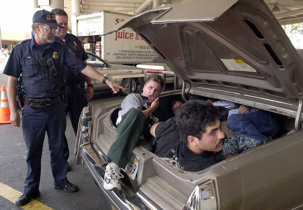 . U.S. Customs Service inspectors open the trunk of a car carrying five suspected illegal immigrants at the San Ysidro Port of Entry on Wednesday, Sept. 20, 2000 in San Diego. The supected smuggler driving the car crashed into a pole while trying to evade authorities after running the border from Mexico. Smugglers are trying more frequently to use cars to bring illegal immigrants into the United States because of increased efforts by the U.S Border Patrol to stop illegal crossings on foot. The five were taken into custody. (AP Photo/Denis Poroy)