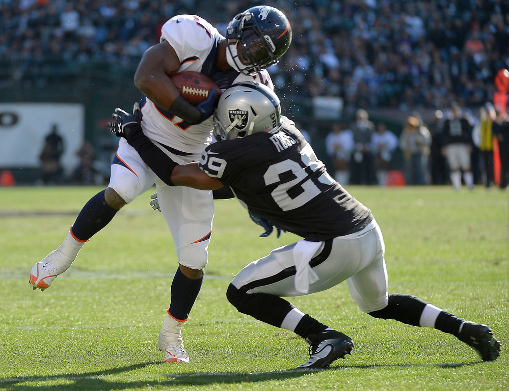 . Denver Broncos running back Knowshon Moreno (27) gets hit by Oakland Raiders strong safety Brandian Ross (29) after a short gain during the first quarter at O.co Coliseum. (Photo by John Leyba/The Denver Post)