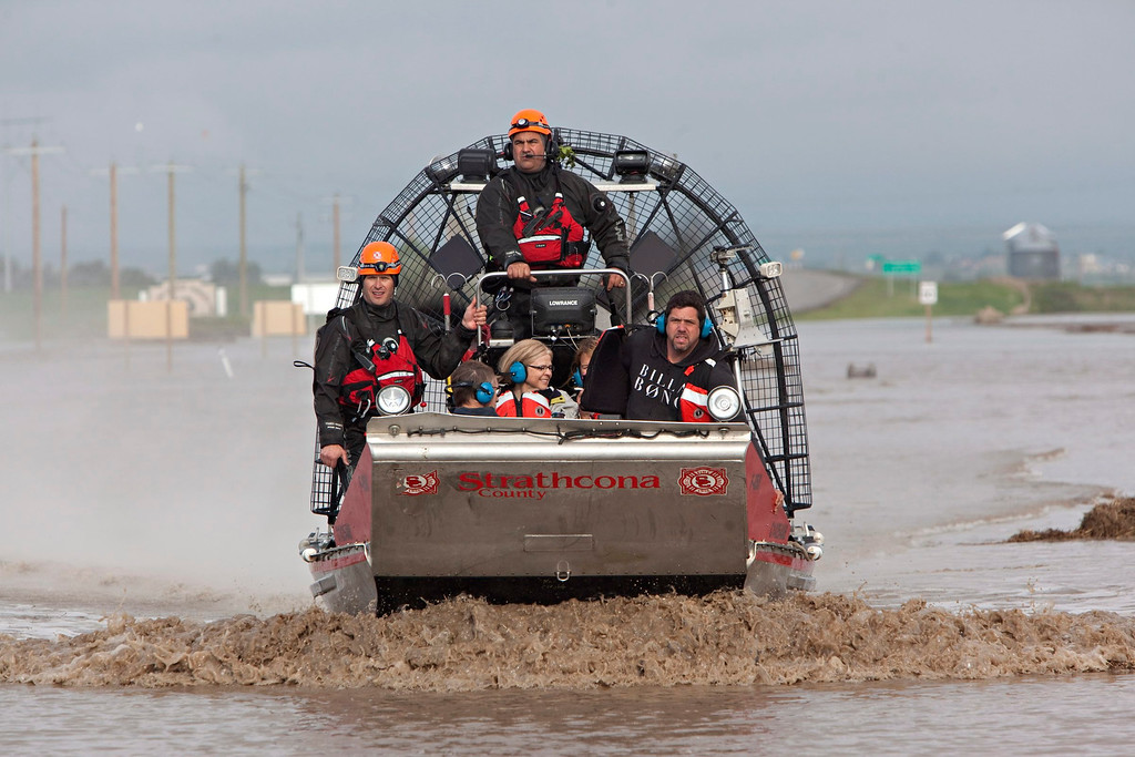 . A search and rescue boat carries rescued passengers from a flooded industrial site near highway 543 north of High River, Alberta, Canada on Friday, June 21, 2013. The rescued passengers spent the night moored on a structure they built in the water.  Calgary\'s mayor said Friday the flooding situation in his city is as under control as it can be, for now. Officials estimated 75,000 people have been displaced in the western Canadian city. Mayor Naheed Nenshi said the Elbow River, one of two rivers that flow through the southern Alberta city, has peaked.  (AP Photo/The Canadian Press, Jordan Verlage)