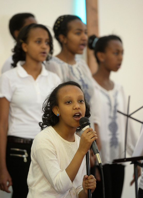 . AURORA, CO. - JANUARY 11:  Addis Kidan Evangelical Church children\'s choir member, Debora Abera, 12, leads the choir during her church dedication service Saturday morning, January 10, 2014. (Photo By Andy Cross / The Denver Post)