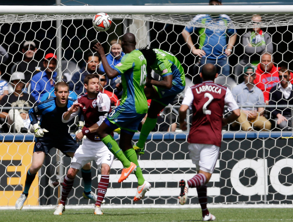 . Seattle Sounders\' Obafemi Martins, second from right, and Djimi Traore (18) try to head the ball as Colorado Rapids goalkeeper Clint Irwin, left, and defender Drew Moor (3) look on, Saturday, April 26, 2014, in the first half of an MLS soccer match in Seattle. (AP Photo/Ted S. Warren)