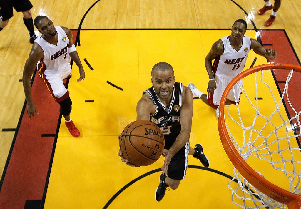 . San Antonio Spurs guard Tony Parker (9) drives to the basket over Miami Heat center Chris Bosh (1) and guard Mario Chalmers (15),  during the first half in Game 3 of the NBA basketball finals, Tuesday, June 10, 2014, in Miami. (AP Photo/Wilfredo Lee)