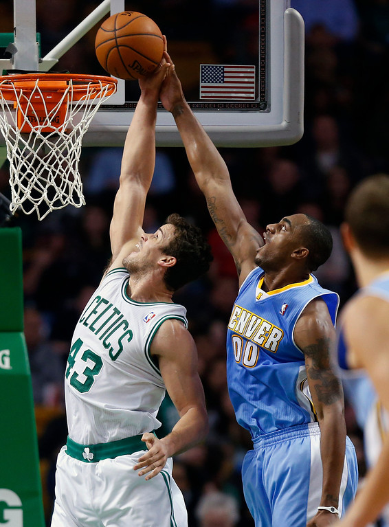 . Denver Nuggets\' Darrell Arthur (00) blocks a shot by Boston Celtics\' Kris Humphries (43) in the second quarter of an NBA basketball game in Boston, Friday, Dec. 6, 2013. (AP Photo/Michael Dwyer)