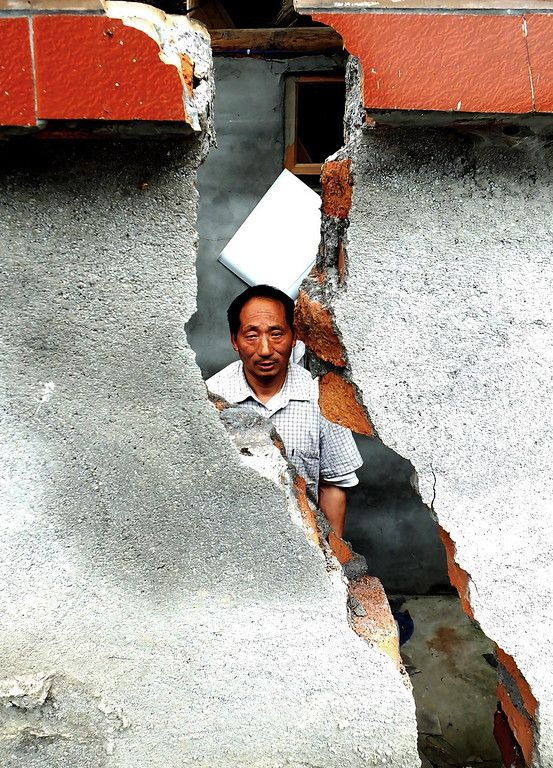 . This photo taken on April 24, 2013 shows an earthquake victim standing before his damaged home in Taiping township in Lushan county of Yaan, southwest China\'s Sichuan province.  Tens of thousands of homeless survivors of China\'s devastating quake are living in makeshift tents or on the streets, facing shortages of food and supplies as well as an uncertain future. AFP/Getty Images