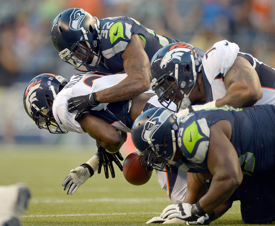 . SEATTLE, WA. - AUGUST 17: Denver Broncos running back Ronnie Hillman (21) loses control of the ball as Seattle Seahawks strong safety Jeron Johnson (32) makes the tackle during the second quarter August 17, 2013 at Century Link Field. Hillman recovered the ball on the play. (Photo By John Leyba/The Denver Post)