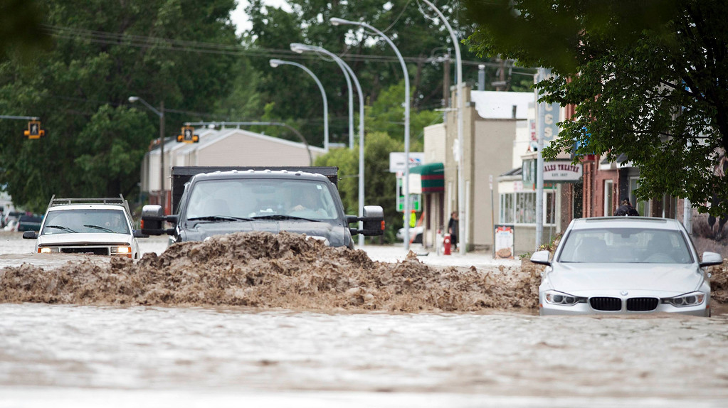 . Cars drive through rising floodwaters in downtown High River in Alberta province June 20, 2013. A state of emergency has been issued for the town of High River, which is being evacuated due to floods. REUTERS/Mike Sturk