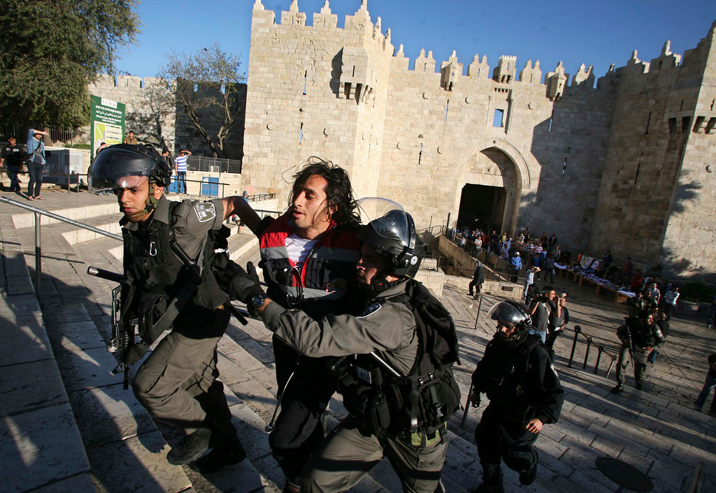 . Israeli border policemen remove a Palestinian medic during clashes at a protest, held without a police permit, outside Jerusalem\'s Old City April 2, 2013. The protest took place following the death of Maysara Abu Hamdeya, a Palestinian inmate who died from cancer in an Israeli hospital on Tuesday. Hamdeya\'s death also threatened to raise tensions in the Israeli-occupied West Bank, where Palestinians, who view jailed brethren as heroes in a fight for statehood, have held several protests in recent weeks in support of prisoners. REUTERS/Muammar Awad
