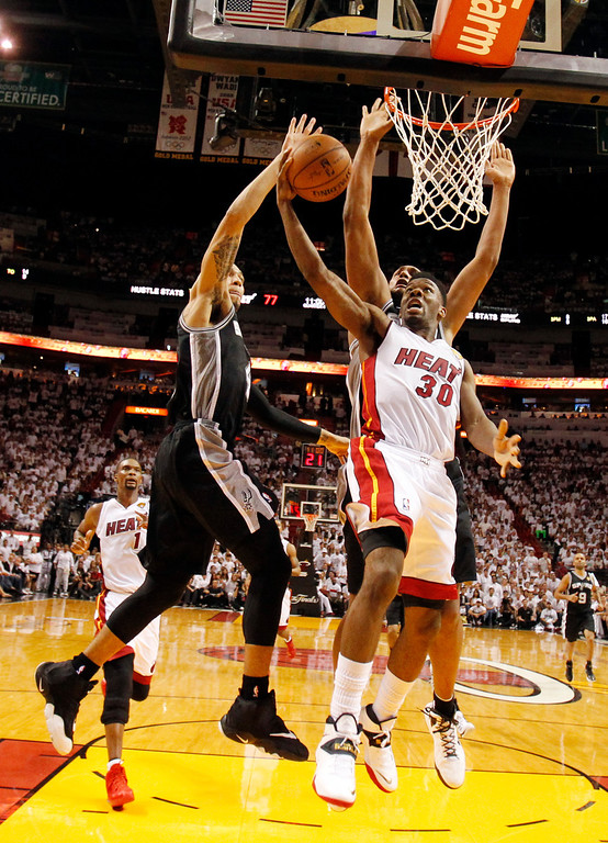 . San Antonio Spurs guard Danny Green (4) and San Antonio Spurs forward Boris Diaw (33), block a shot to the basket by Miami Heat guard Norris Cole (30), during the second half in Game 3 of the NBA basketball finals, Tuesday, June 10, 2014, in Miami. The Spurs defeated the Heat 111-92. (AP Photo/Wilfredo Lee)