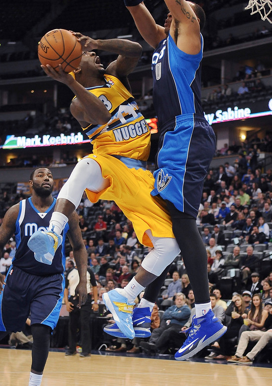 . Denver Nuggets point guard Ty Lawson is fouled by Shawn Marion of the Dallas Mavericks in the first quarter Wednesday night at the Pepsi Center. (Photo By Steve Nehf / The Denver Post)