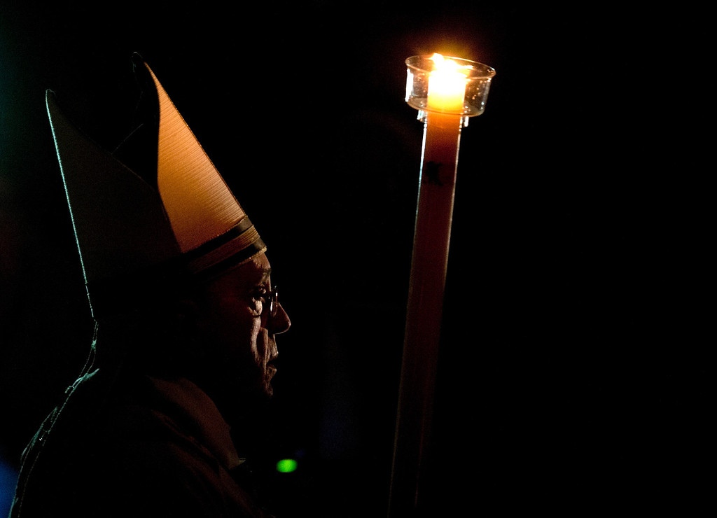 . Pope Francis holding a tall, lit, white candle, enters a darkened St. Peter\'s Basilica to begin the Easter vigil service, at the Vatican, Saturday, April 19, 2014. (AP Photo/Alessandra Tarantino)