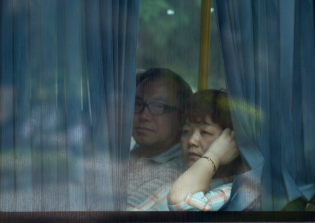 """. Chinese relatives of passengers from the missing Malaysia Airlines flight MH370 leave from a resort on a bus in Cyberjaya, outside Kuala Lumpur on March 21, 2014. Surveillance aircraft scoured a remote and stormy section of the Indian Ocean on March 20 for a pair of floating objects that Australia and Malaysia guardedly called a \""""credible\"""" lead in the 12-day-old hunt for the missing passenger jet. AFP PHOTO / MOHD RASFAN/AFP/Getty Images"""