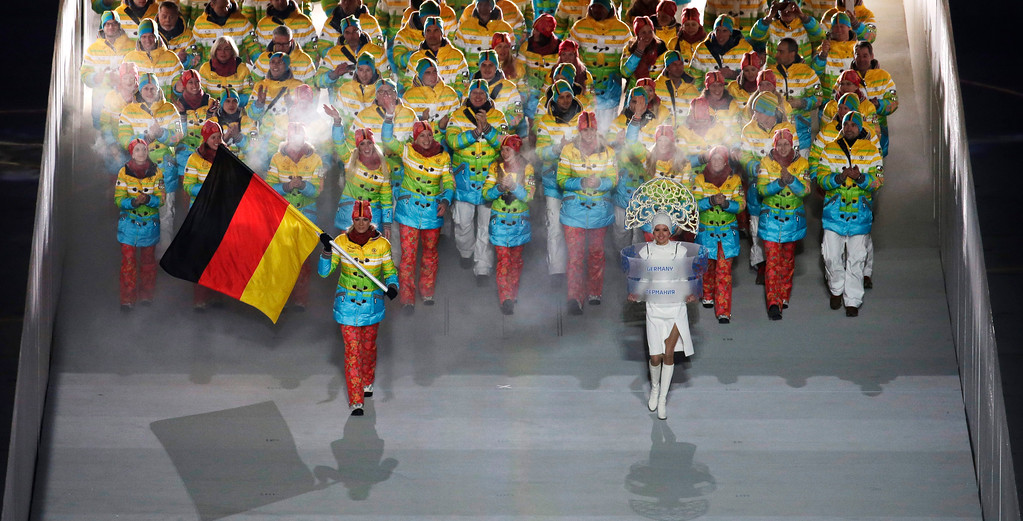 . Maria Hoefl-Riesch of Germany holds her national flag and enters the arena with teammates during the opening ceremony of the 2014 Winter Olympics in Sochi, Russia, Friday, Feb. 7, 2014. (AP Photo/Charlie Riedel)