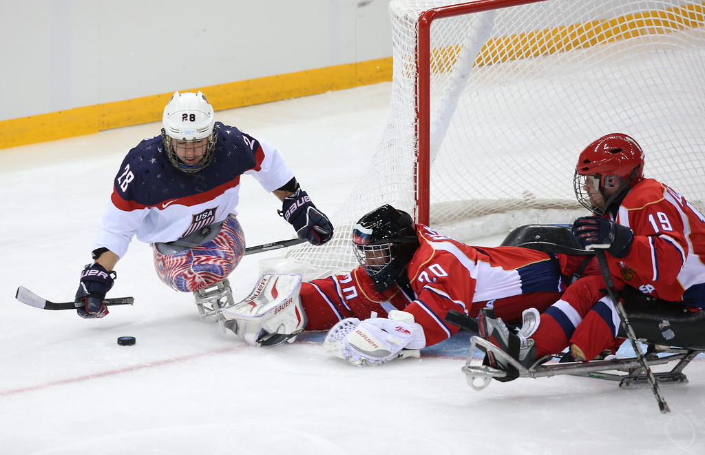 . Paul Schausr (L) of the USA attacks, as Vladimir Kamantcev (C) and Ivan Kuznetsov (R) of Russia defend the goal  during the Ice Sledge Hockey final  match at Sochi 2014 Paralympic Games, Russia, 15 March 2014.  EPA/SERGEI CHIRIKOV