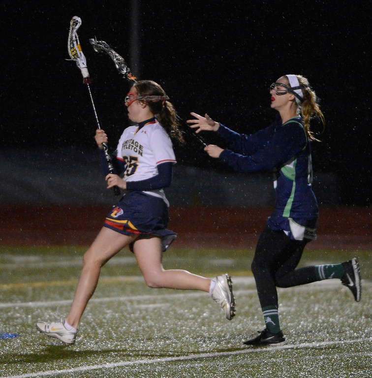 . LITTLETON, CO - MAY 8: Hallie Kurtz, left, Heritage/Littleton, runs towards the goal against the defense of Shelby Squire, ThunderRidge High School, heads down field against Bailey Dodd, Heritage/Littleton, during the second half of play at Littleton Public Schools Stadium for the first round of the 2013 Colorado Girls State Lacrosse Championships May 8, 2013. ThunderRidge won 8-5. (Photo By Andy Cross/The Denver Post)