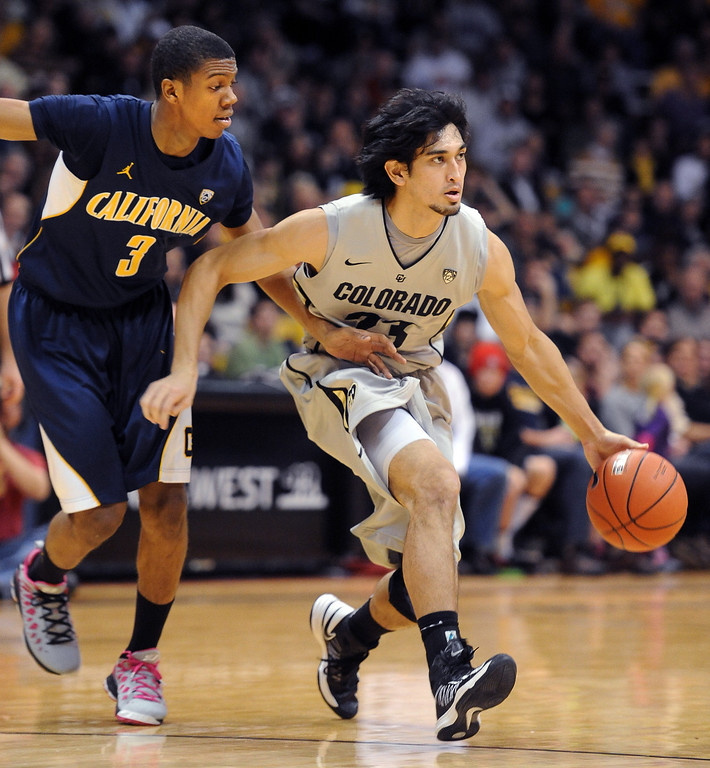 . Sabatino Chen of CU drives around Tyrone Wallace of Cal during the first half of the January 27th, 2013 game in Boulder. Cliff Grassmick/The Daily Camera