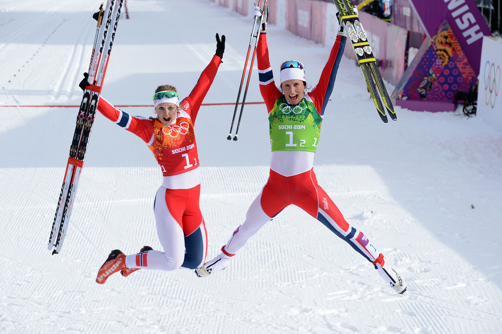 . (LtoR) Norway\'s Ingvild Flugstad Oestberg and Norway\'s Marit Bjoergen celebrate after the Women\'s Cross-Country Skiing Team Sprint Classic Final at the Laura Cross-Country Ski and Biathlon Center during the Sochi Winter Olympics on February 19, 2014 in Rosa Khutor near Sochi. KIRILL KUDRYAVTSEV/AFP/Getty Images