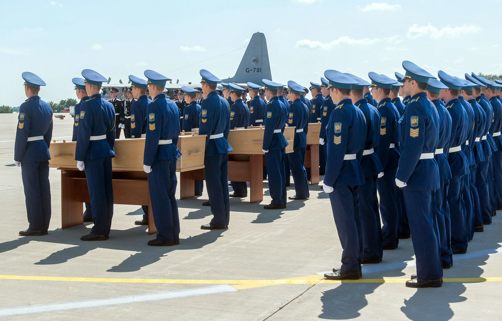 . Ukrainian soldiers stand next to coffins carrying the remains of victims of the Malaysia Airlines flight MH17 crash during a ceremony at the airport of Kharkiv, Ukraine, on July 23, 2014. The first plane carrying bodies from downed Malaysia Airlines flight MH17 left eastern Ukraine for the Netherlands on July 23 following a sombre ceremony. The Dutch military aircraft took off from the airport in the government-controlled city of Kharkiv bound for Eindhoven after the first group of victims\' remains were loaded onto the plane in wooden coffins.  AFP PHOTO/ SERGEY BOBOK/AFP/Getty Images