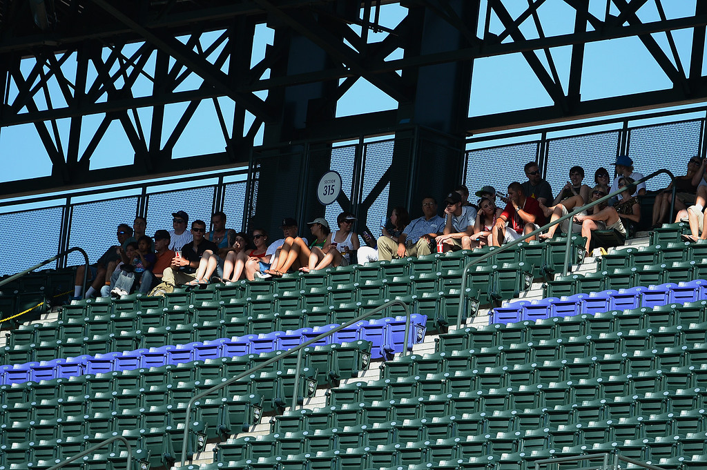 . Fans try to avoid the sun and heat during the game between the New York Mets and the Colorado Rockies at Coors Field on June 27, 2013 in Denver, Colorado. Photo by Garrett W. Ellwood/Getty Images)