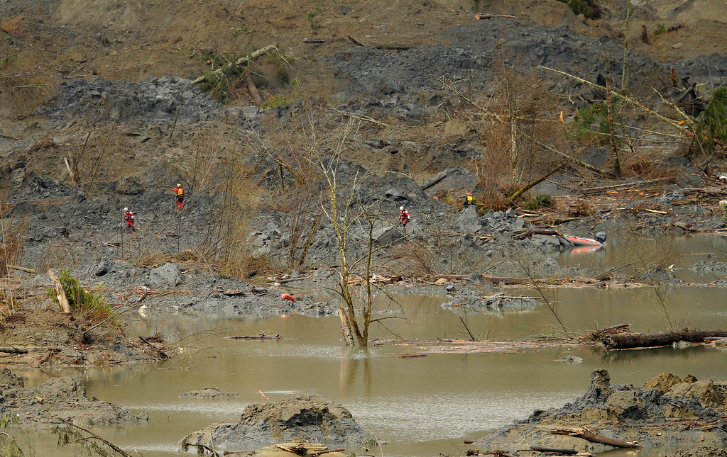 . Search workers wearing red are dwarfed by the mud and debris filled landscape they were searching Thursday, March 27, 2014, where a massive mudslide struck Saturday near Darrington, Wash. The searchers shown had to use a boat to reach the area shown. (AP Photo/Ted S. Warren, Pool)