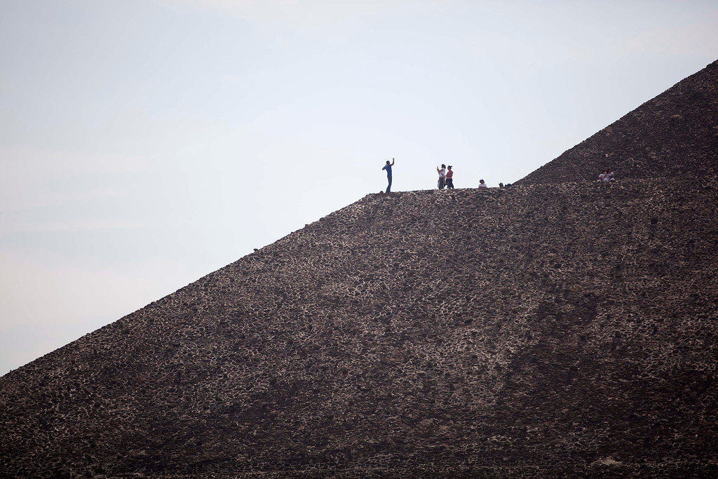 . A man poses for photos as he stands on the Pyramid of the Sun on the day of the spring equinox in Teotihuacan, Mexico, Thursday, March 21, 2013. The spring equinox marks the beginning of the spring season. (AP Photo/Alexandre Meneghini)