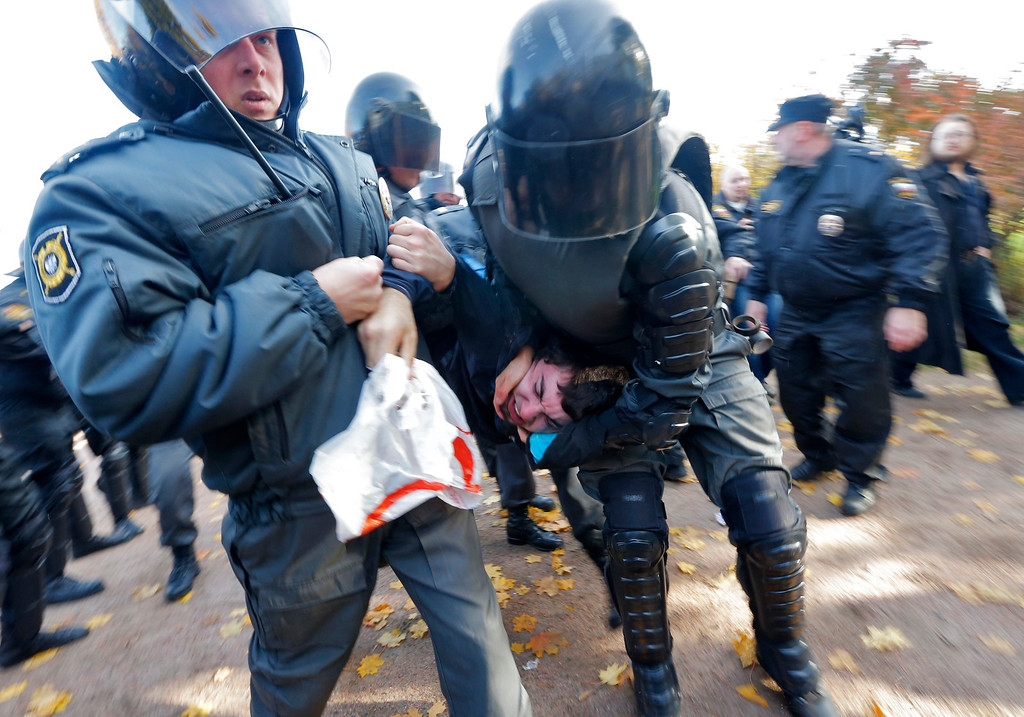. Riot police detain an anti-gay protester during an authorized gay rights rally in St. Petersburg, Russia, Saturday, Oct. 12, 2013. A gay rights rally in St. Petersburg has ended in scuffles after several dozen protesters were confronted by about 200 conservative and religious activists. The police standing nearby waited until clashes broke out between the two groups before intervening. According to Russian news agencies, the police detained 67 people from both sides. (AP Photo/Dmitry Lovetsky)
