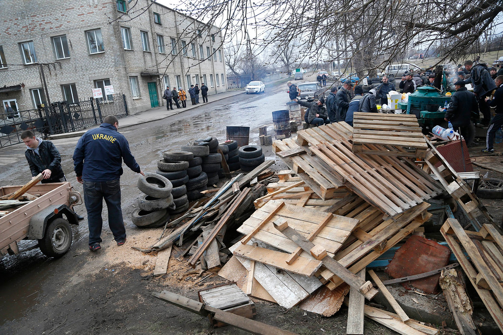 . Pro Russian activists collect wood  in their camp near the armory of Ukrainian army where they take a stand to prevent the export of arms and ammunition in the village of Poraskoveyevka, eastern Ukraine, Thursday, March 20, 2014. T(AP Photo/Sergei Grits)