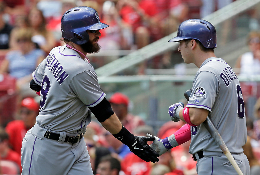 . Colorado Rockies\' Corey Dickerson, right, congratulates Charlie Blackmon, left,  after Blackmon hit a solo home run off Cincinnati Reds starting pitcher Homer Bailey in the fourth inning of a baseball game, Sunday, May 11, 2014, in Cincinnati. (AP Photo/Al Behrman)