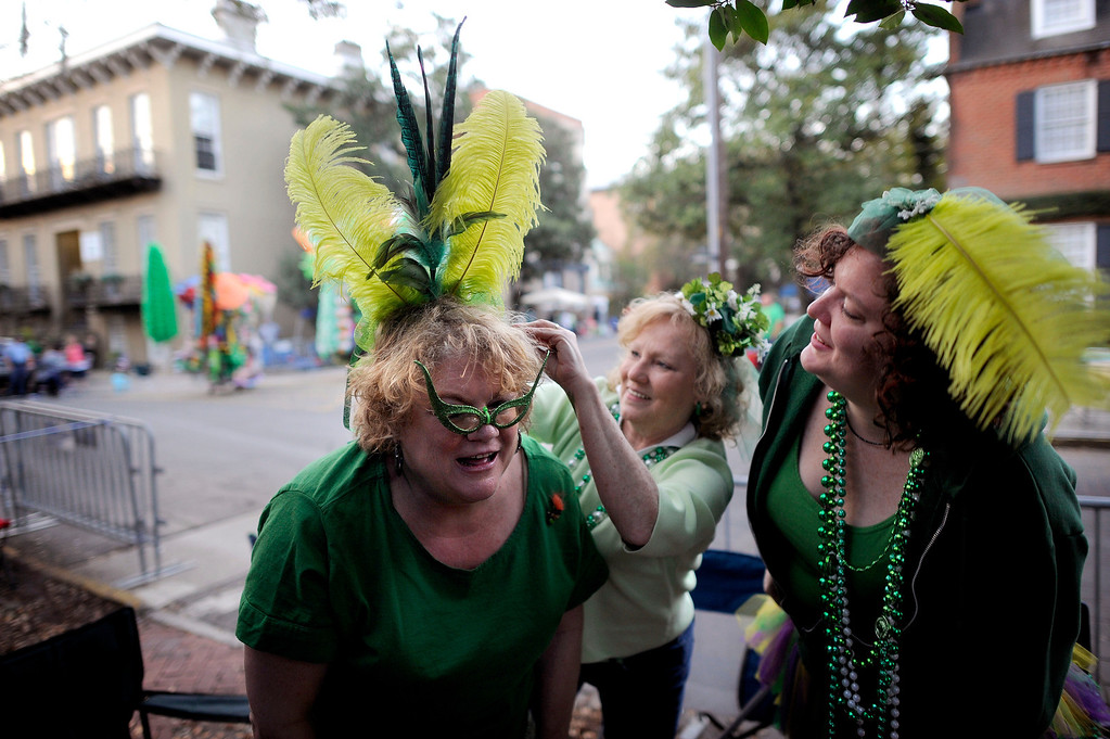 . Bev Kehayes, left, of Greensboro, N.C., gets her homemade hat pinned on her head by her friend Mary Parrish, center, and Sara Farnsworth, right, before Savannahís 189-year-old St. Patrickís Day parade, Saturday, March 16, 2013, in Savannah, Ga. St. Patrick\'s Day falls on March 17, which is Sunday. But a number of cities, including Savannah, New York and Chicago are all holding parades Saturday to take advantage of the full weekend. (AP Photo/Stephen Morton)