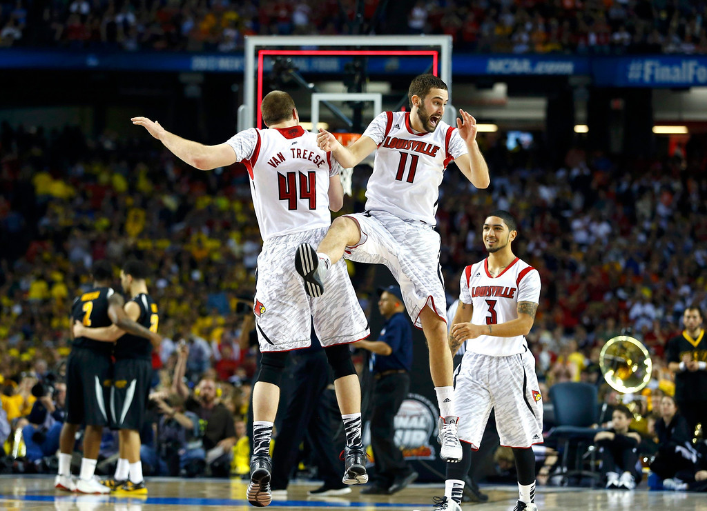 . Louisville Cardinals\' Luke Hancock (11) celebrates with teammates Stephan Van Treese (44) and Peyton Siva after they defeated the Wichita State Shockers in their NCAA men\'s Final Four basketball game in Atlanta, Georgia April 6, 2013.  REUTERS/Chris Keane