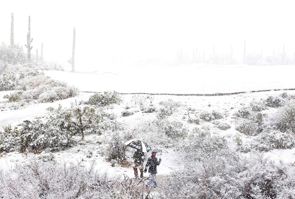 . Golf spectators look for cover as snow forces suspension of play during the first round of the WGC-Accenture Match Play Championship golf tournament in Marana, Arizona February 20, 2013. Play was suspended at 1807 GMT because of driving rain and snow in the opening round of the WGC-Accenture Match Play Championship on Wednesday. REUTERS/Matt Sullivan