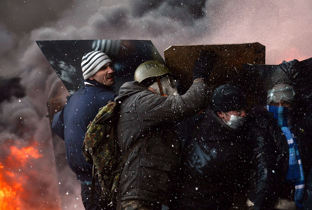 . Ukrainian demonstrators take cover during clashes between pro-EU opposition supporters and riot police in central Kiev on January 23, 2014.  AFP PHOTO / VASILY MAXIMOV/AFP/Getty Images