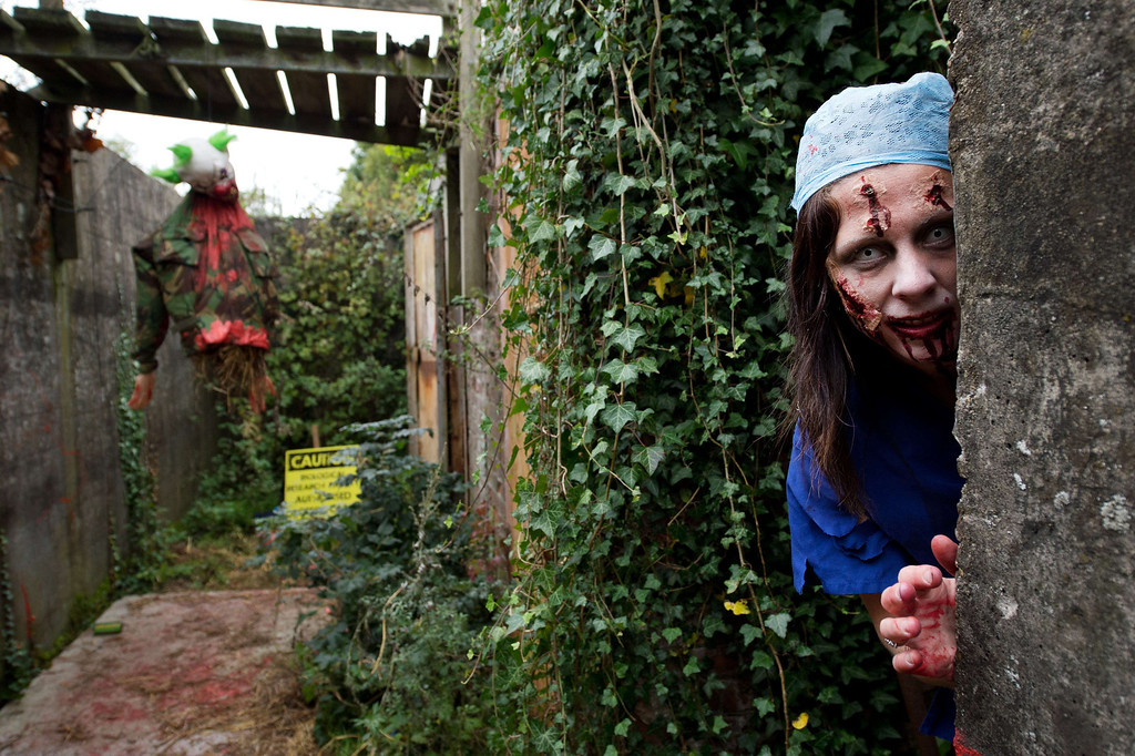 ". A volunteer ""zombie\"" poses for a picture as she waits for participants during one of Britain\'s biggest horror events, the \""Zombie Evacuation Race\"" at Carver Barracks near Saffron Walden, England, on October 5, 2013. The race sees thousands of participants attempt to complete a gruelling 5 kilometre cross-country run, while evading \""zombies\"", intent on snatching the three life-line strips hanging from every runner\'s waist.  Those who manage to get through with any strips remaining are named as survivors while those without take home an \""infected\"" badge.  LEON NEAL/AFP/Getty Images"