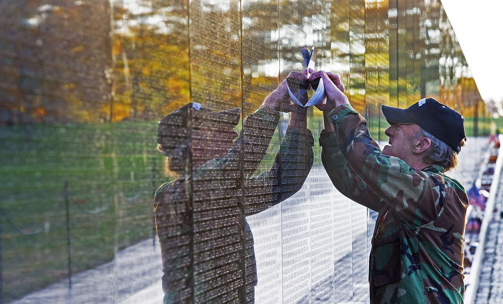 . An unidentified Viet Nam veteran traces a name off a fallen soldier off the Viet Nam Memorial wall seen here on  Veteran\'s Day November 11, 2013  as he pays his respects in Washington, DC.    PAUL J. RICHARDS/AFP/Getty Images