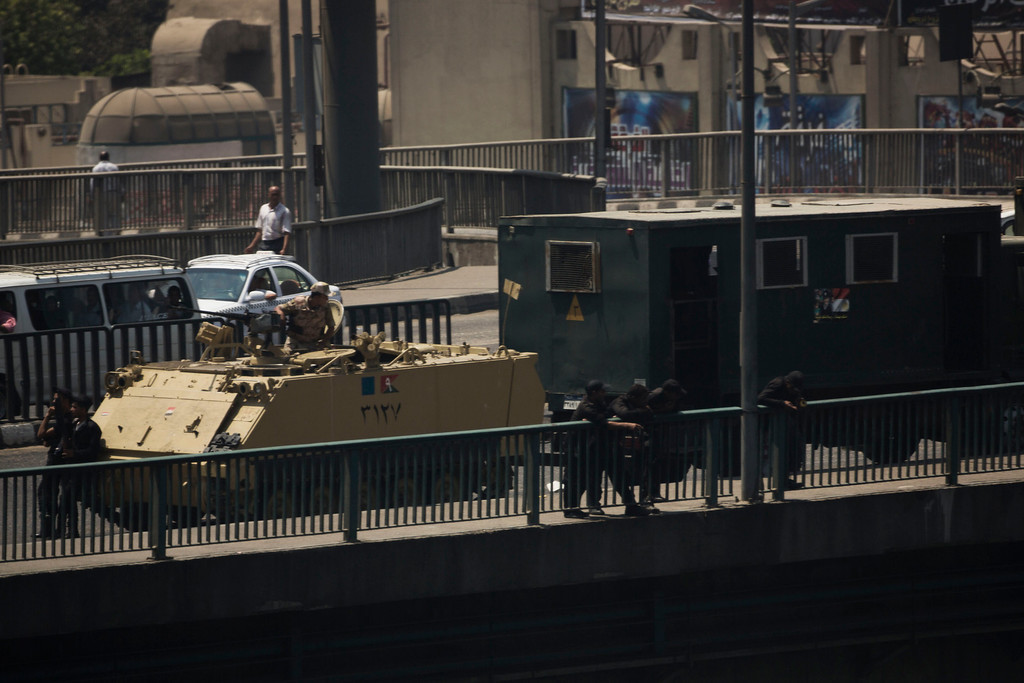 . An Egyptian army armored vehicle and a riot police truck are seen on a bridge over the Nile river at Zamalek District in Cairo, Egypt, Saturday, Aug. 17, 2013. Authorities say police in Cairo are negotiating with people barricaded in a mosque and promising them safe passage if they leave. Muslim Brotherhood supporters of Egypt\'s ousted Islamist president Mohamed Morsi are vowing to defy a state of emergency with new protests today, adding to the tension. (AP Photo/Manu Brabo)