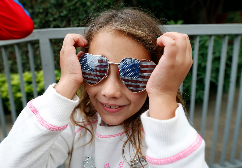 . Alinee Aquino, 7, of San Diego, wears United States themed sunglasses outside of the Sao Paulo FC training center where the U.S. is holding its training in Sao Paulo, Brazil, Wednesday, June 11, 2014. The U.S. will play in group G of the 2014 soccer World Cup. (AP Photo/Julio Cortez)