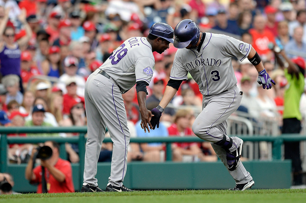 . Michael Cuddyer #3 of the Colorado Rockies celebrates with third base coach Stu Cole #39 after hitting a solo home run in the second inning during a game against the Washington Nationals at Nationals Park on June 23, 2013 in Washington, DC.  (Photo by Patrick McDermott/Getty Images)