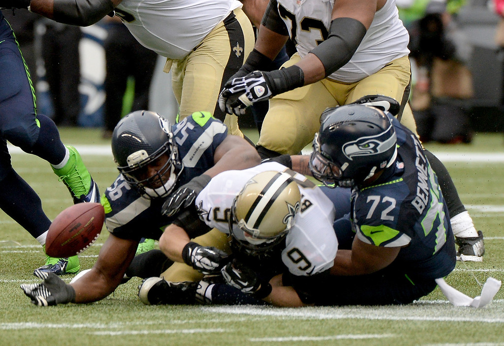 . SEATTLE, WA - JANUARY 11:  Quarterback Drew Brees #9 of the New Orleans Saints is sacked by defensive end Cliff Avril #56 and defensive end Michael Bennett #72 of the Seattle Seahawks in the third quarter during the NFC Divisional Playoff Game at CenturyLink Field on January 11, 2014 in Seattle, Washington.  (Photo by Harry How/Getty Images)