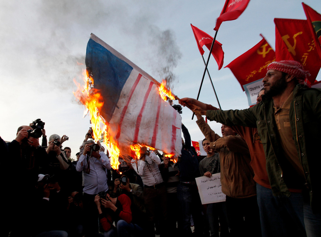 . A Jordanian activist burns a representation of a U.S. flag, during a protest in front of the U.S. embassy against a visit by President Barack Obama to the kingdom, in Amman, Jordan, Thursday, March 21, 2013. (AP Photo/Mohammad Hannon)