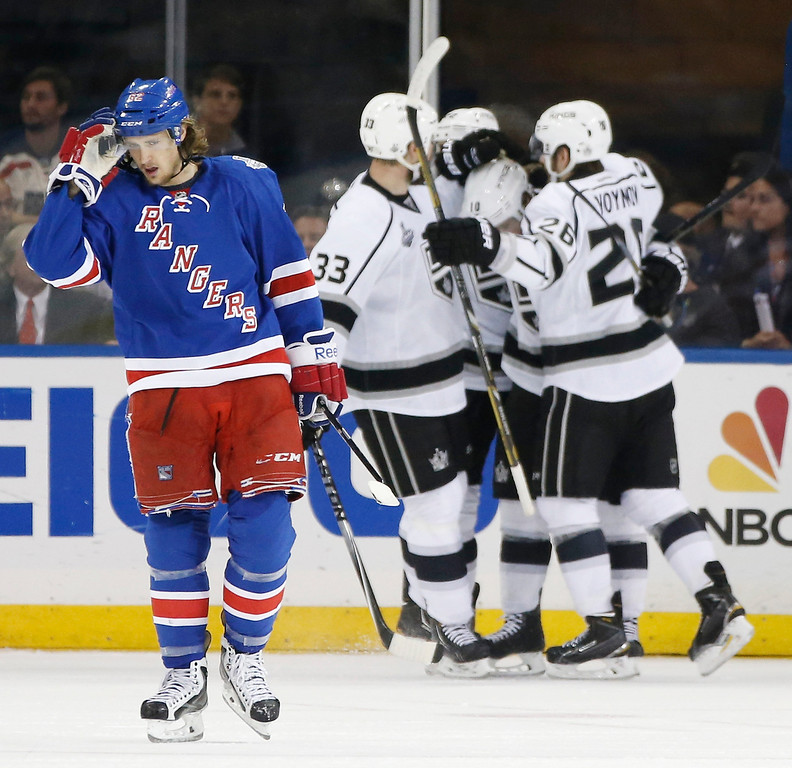 . New York Rangers Carl Hagelin (62), left, reacts as the Los Angeles Kings Willie Mitchell (33) and Slava Voynov (26), celebrate a second period goal by Mike Richards, center, during Game 3 of the NHL hockey Stanley Cup Final, Monday, June 9, 2014, in New York. (AP Photo/Kathy Willens)