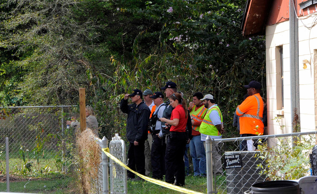 . Rescue and engineering crews watch from a neighboring backyard as other crew members work to evaluate the safety of a home where a sinkhole opened up and swallowed a man in Seffner, Florida, March 1, 2013. REUTERS/Brian Blanco