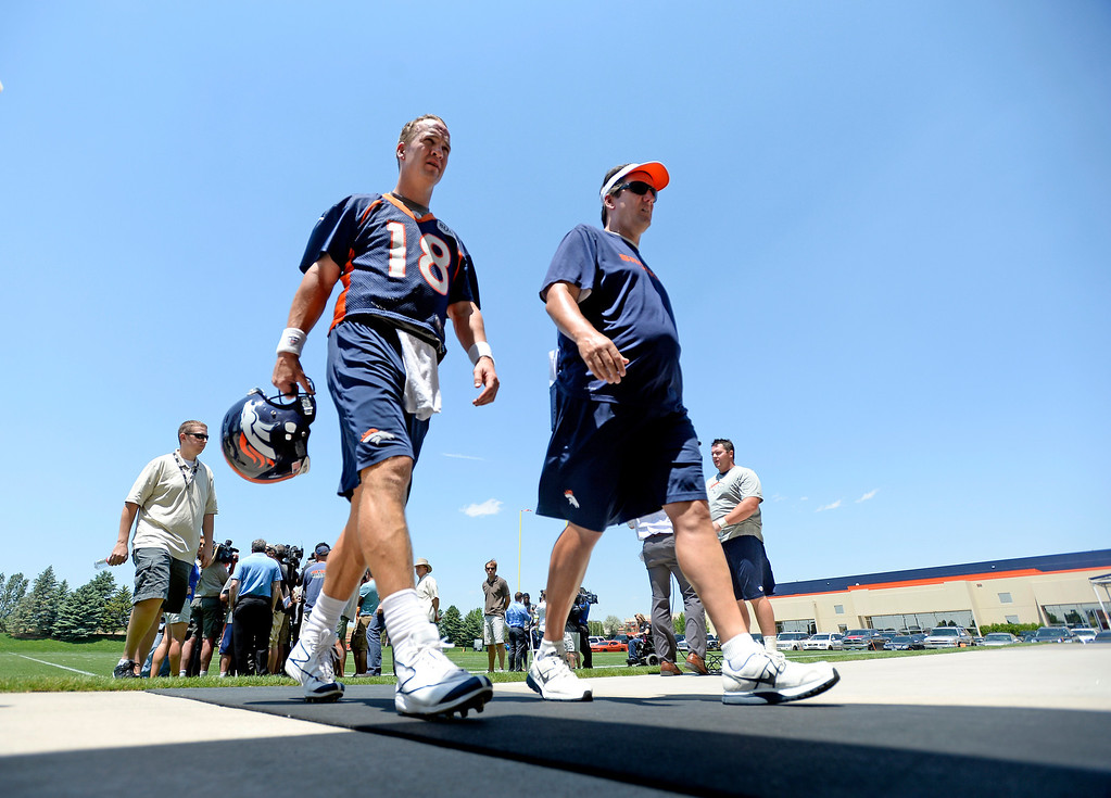 . Peyton Manning (18) quarterback of the Denver Broncos  walks off the field with quarterbacks coach Greg Knapp after the first day of mini camp June 11, 2013 at Dove Valley. (Photo By John Leyba/The Denver Post)