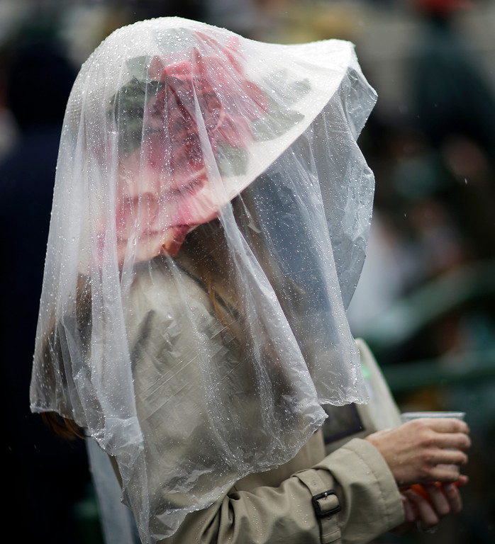 . A spectator protects her fancy hat from the rain before the 139th Kentucky Derby at Churchill Downs Saturday, May 4, 2013, in Louisville, Ky. (AP Photo/David Goldman)